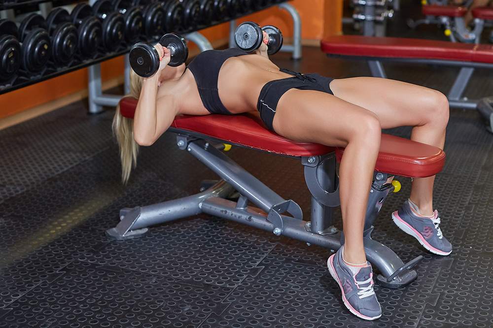 Young,Sports,Woman,Doing,Exercises,With,Dumbbells,In,The,Gym.